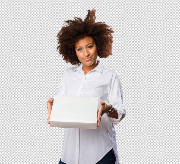 Giovane donna di colore che tiene una scatola bianca