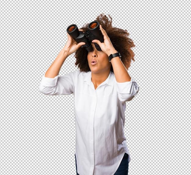 Giovane donna di colore che osserva tramite il binocolo