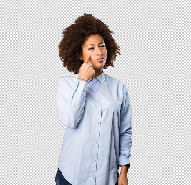 Giovane donna di colore che punta il suo occhio
