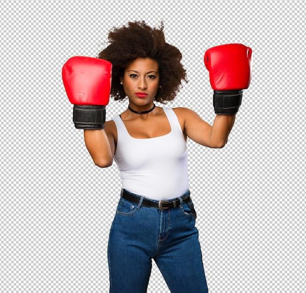 Giovane donna di colore che usando i guantoni da pugile