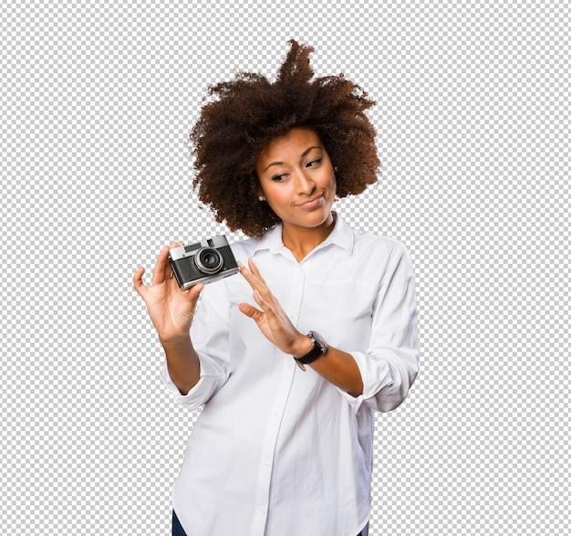 Giovane donna di colore che per mezzo di una macchina fotografica d'annata