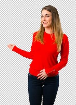 Giovane donna bionda che punta indietro con il dito indice