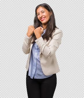 Giovane donna d'affari indiana molto felice ed eccitata, alzando le braccia, celebrando una vittoria o un successo, vincendo alla lotteria