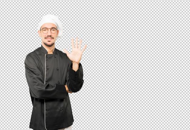 Giovane chef facendo un gesto numero cinque