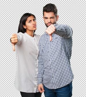 Le giovani coppie che fanno un pollice giù gesticolano
