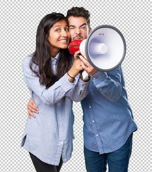 Giovani coppie che gridano con un megafono