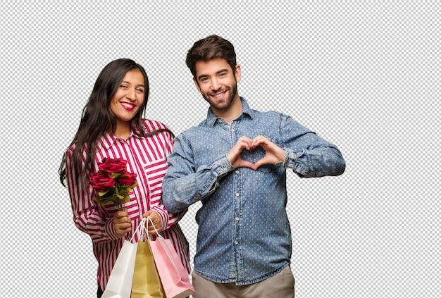 Giovane coppia in giorno di san valentino facendo un cuore forma con le mani