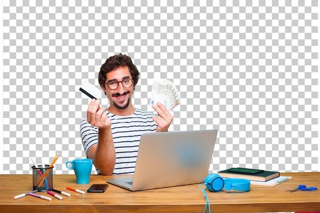 Giovane grafico pazzo su una scrivania con un concetto di laptop e paga, acquisto o denaro