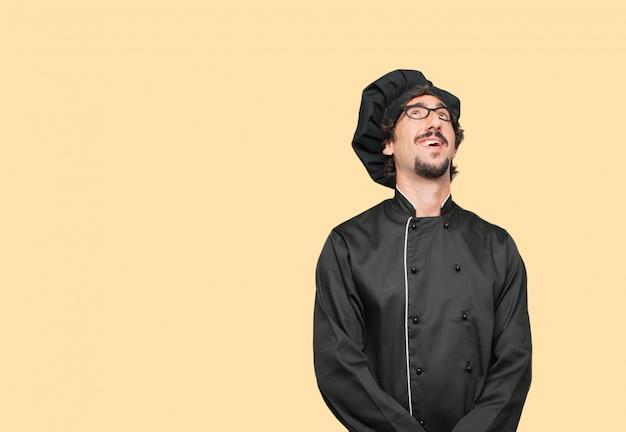 Giovane pazzo come uno chef sorridente e guardando in alto, verso il cielo