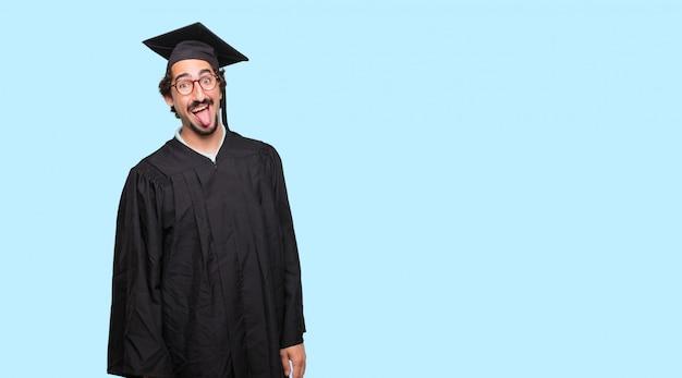 Giovane uomo laureato che scherza, tira fuori la lingua con un'espressione divertente, sciocca e giocosa