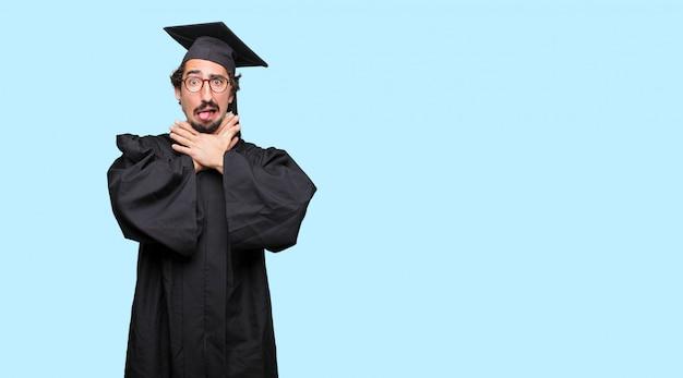 Giovane uomo laureato con un gesto stressato, sudando e tirando il collo della camicia aperto, sentendosi soffocato.