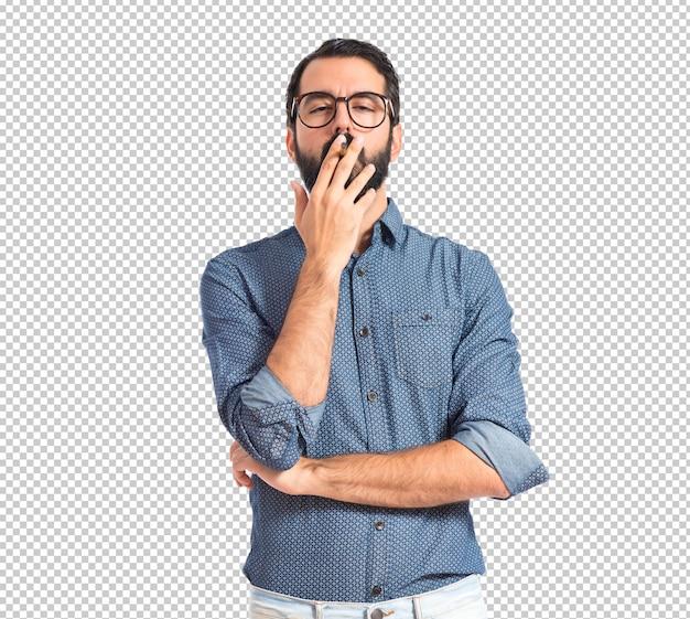 Uomo giovane hipster che fuma sopra priorità bassa bianca