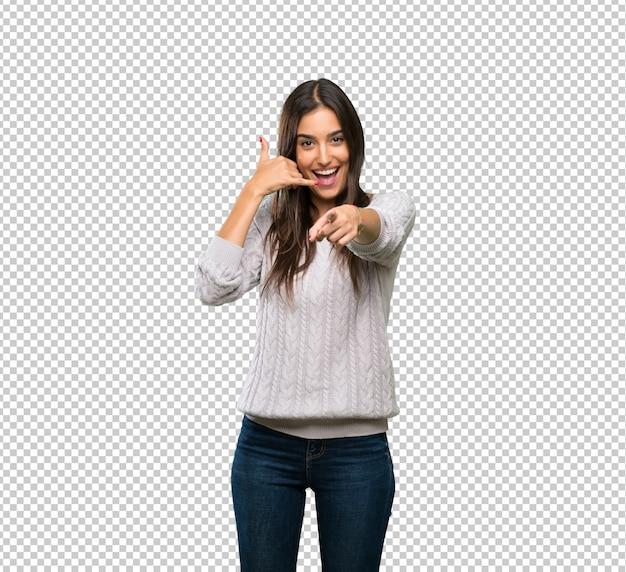 Giovane donna ispanica del brunette che fa gesto del telefono e che indica fronte