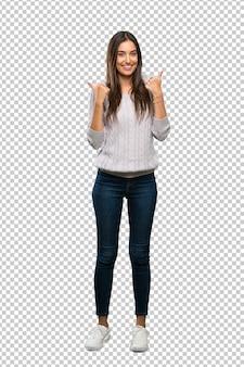La giovane donna ispanica del brunette con i pollici aumenta il gesto e sorridere