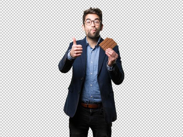 Giovane uomo che mangia una barretta di cioccolato