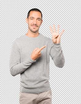 Giovane che fa un gesto di numero quattro