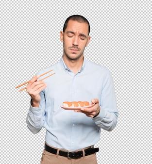 Giovane che utilizza le bacchette per mangiare il sushi