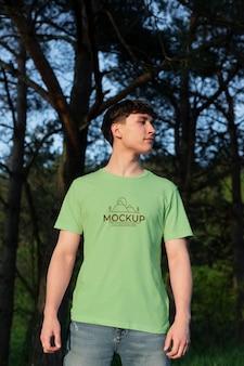 Giovane che indossa una t-shirt mock-up all'esterno Psd Premium