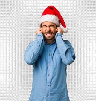 Giovane che indossa le orecchie della copertura del cappello di santa con le mani