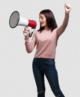 Giovane bella donna eccitata ed euforica, che grida con un megafono, segno di rivoluzione e cambiamento, incoraggiando altre persone a muoversi, personalità di leader