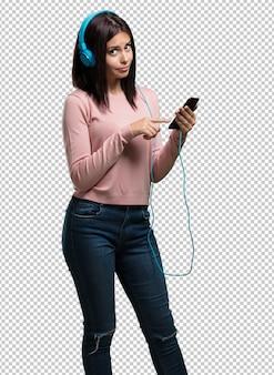 Giovane bella donna rilassata e concentrata, ascoltando musica con il suo telefono cellulare, sentendo il ritmo e scoprendo nuovi artisti, gli occhi chiusi