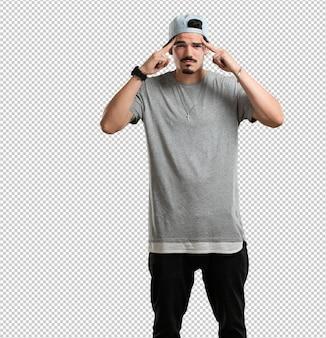 Giovane rapper uomo uomo che fa un gesto di concentrazione, guardando dritto concentrato su un obiettivo