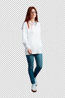 Giovane ragazza rossa in una felpa bianca urbana con occhiali a piedi. gesto di movimento