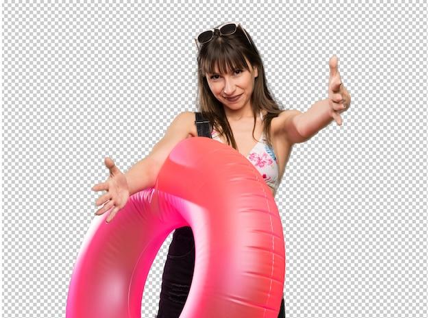 Giovane donna in bikini che presenta e che invita a venire con la mano