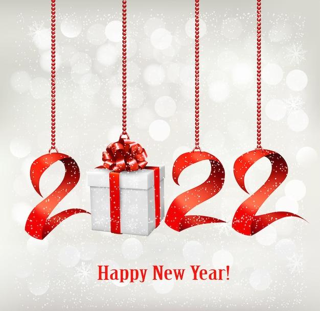 Sfondo di capodanno 2022 con confezione regalo e nastri rossi. vettore.