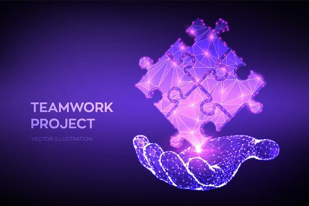 Elementi di puzzle astratti poligonali bassi 3d in mano. simbolo di lavoro di squadra, cooperazione, partnership, associazione e connessione.