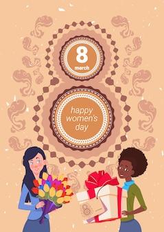 8 marzo ragazze sveglie del fondo di festa che tengono il contenitore di regalo e mazzo di fiori durante il saluto felice di giorno delle donne
