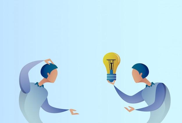 L'uomo astratto di affari che dà collega la nuova idea creativa di concetto tiene la lampadina