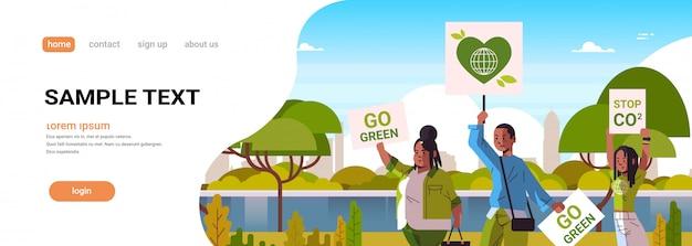 Attivisti tenendo manifesti andare verde salvare pianeta sciopero concetto manifestanti campagna per proteggere la terra dimostrando contro il riscaldamento globale ritratto paesaggio urbano sfondo spazio copia orizzontale