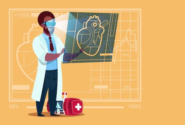 Medico afroamericano cardiologo esaminando digital heart wear realtà virtuale occhiali cliniche ospedale operaio