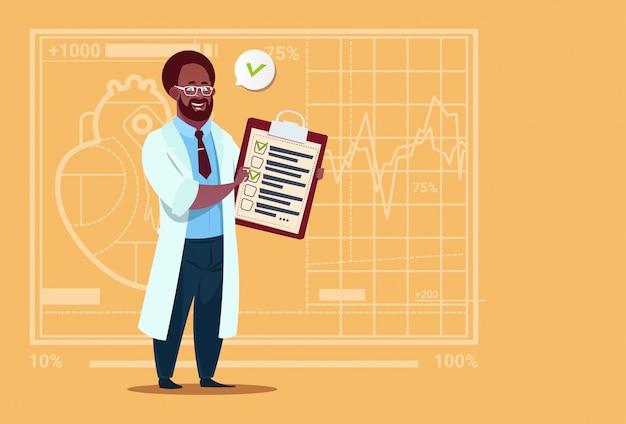 Il dottore afroamericano che tiene la lavagna per appunti con i risultati di analisi e l'ospedale del lavoratore delle cliniche mediche di diagnosi