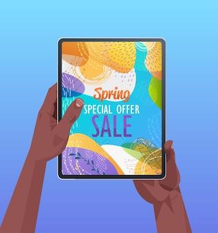Mani umane afroamericane utilizzando tablet pc con volantino banner vendita primavera o biglietto di auguri sullo schermo illustrazione verticale