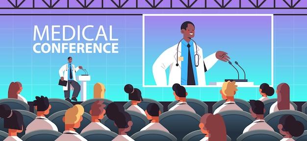 Medico maschio afroamericano che dà discorso alla tribuna con microfono conferenza medica medicina concetto di assistenza sanitaria aula interna illustrazione vettoriale orizzontale