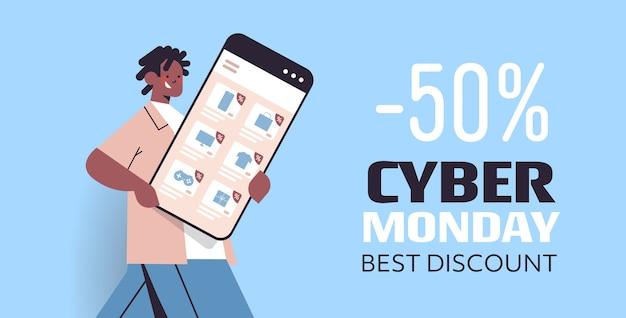 Uomo afroamericano che tiene smartphone shopping online cyber lunedì grande vendita vacanze sconti concetto di commercio elettronico ritratto