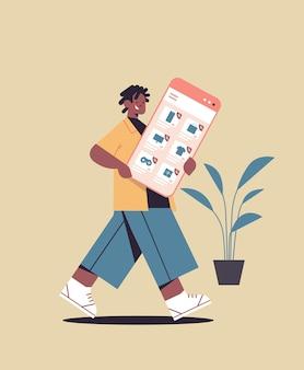 Uomo afroamericano che tiene smartphone shopping online cyber lunedì grande vendita sconti vacanze concetto di e-commerce verticale