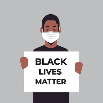 Uomo afroamericano in maschera che tiene la campagna banner materia di vita nera