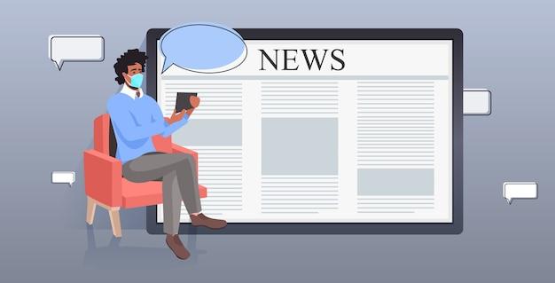 Uomo afroamericano in maschera utilizzando tablet pc leggendo notizie quotidiane giornale online pandemia di coronavirus