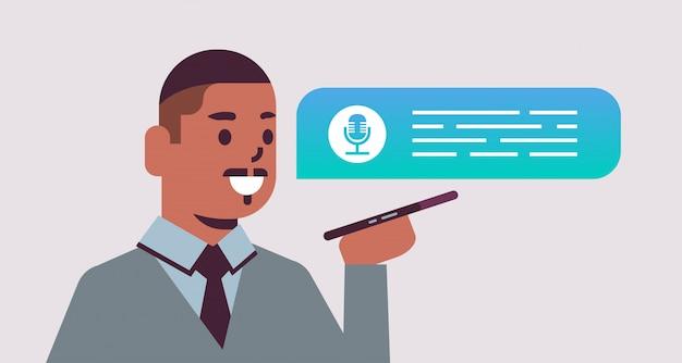 Uomo afroamericano che usando concetto della registrazione del messaggio di comunicazione della rete sociale di applicazione vocale di riconoscimento vocale dell'assistente vocale dello smartphone