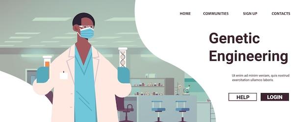 Scienziato afroamericano in maschera che lavora con il dna in provette ricercatore che fa esperimento in laboratorio test del dna diagnosi di ingegneria genetica