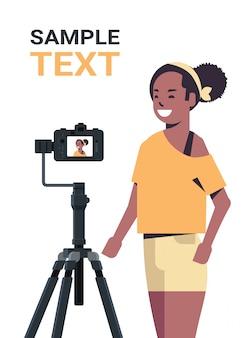 Donna afro-americana blogger registrazione video blog con fotocamera digitale su treppiede streaming live social media blogging concetto verticale spazio copia