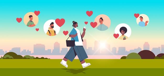 La donna afroamericana che chiacchiera con gli uomini della corsa della miscela nell'incontro online l'app che incontra la relazione sociale comunicazione sociale trova l'amore concetto urbano urbano paesaggio urbano illustrati integrale