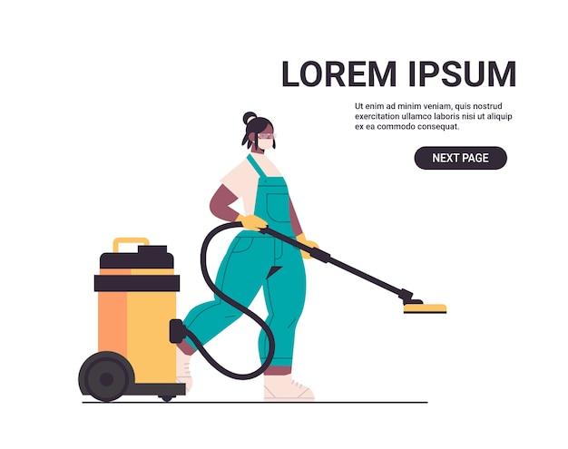 Donna afroamericana bidello in maschera utilizzando aspirapolvere disinfettare le cellule di coronavirus per prevenire la pandemia covid-19 servizio di pulizia copia spazio