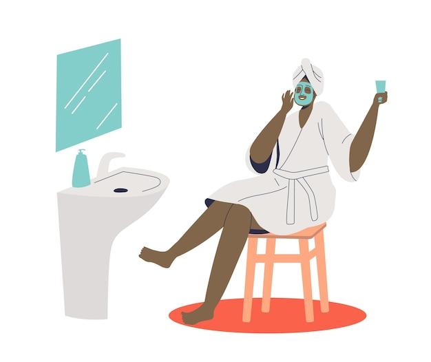 Donna afro-americana che fa procedura di maschera termale cosmetica per la cura della pelle del viso