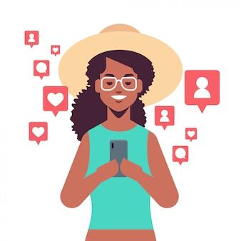 Donna dell'afroamericano che per mezzo dell'applicazione mobile sulle notifiche dello smartphone con il ritratto di concetto di dipendenza digitale dei social network dei commenti dei seguaci di like