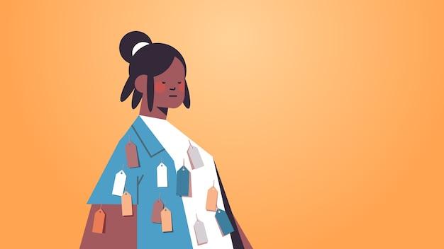 Donna afro-americana con colorfu l tag etichette sul concetto di discriminazione razziale di disuguaglianza di usura personaggio dei cartoni animati femminile