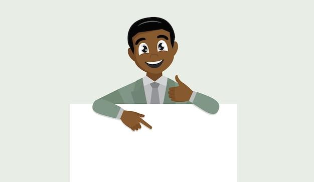 L'uomo africano di affari che mostra l'insegna in bianco, il dito puntato e gesticolando i pollici aumenta il segno.